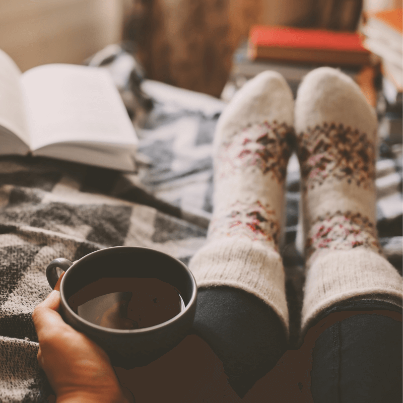 Holding a hot cup of coffee and wearing white socks with red pattern